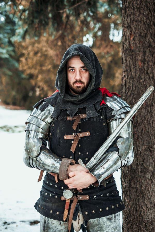 Equipe o cavaleiro com uma espada perto de uma árvore imagens de stock royalty free