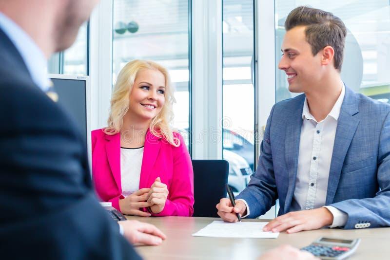 Equipe o contrato de vendas de assinatura para o automóvel no concessionário automóvel imagens de stock royalty free