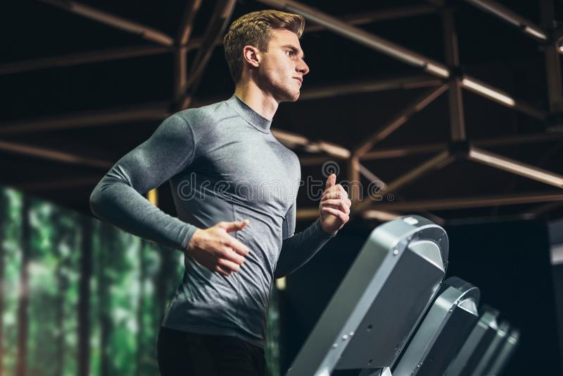 Equipe o corredor em um gym em uma escada rolante foto de stock royalty free