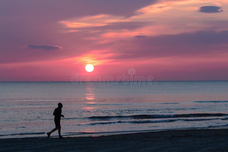 Equipe o corredor na praia quando o sol se ajustar fotografia de stock