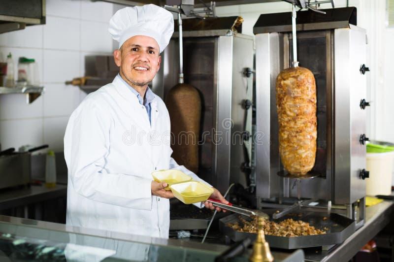 Equipe o cozinheiro que faz o prato do no espeto na cozinha no restaurante do fast food foto de stock
