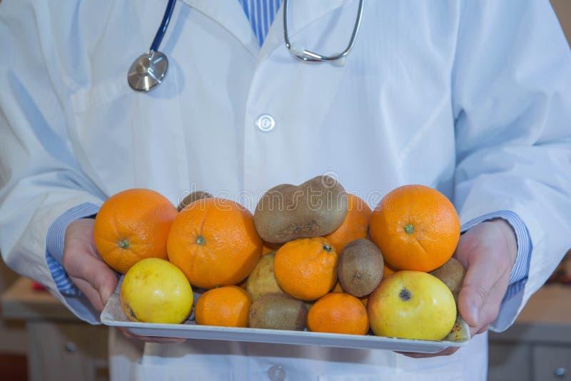 Equipe o doutor de um nutricionista com frutos nas mãos foto de stock