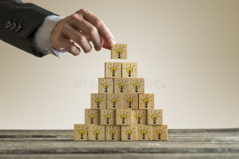 Equipe o empilhamento de uma torre com as ampolas amarelas numa forma de um pyra imagem de stock