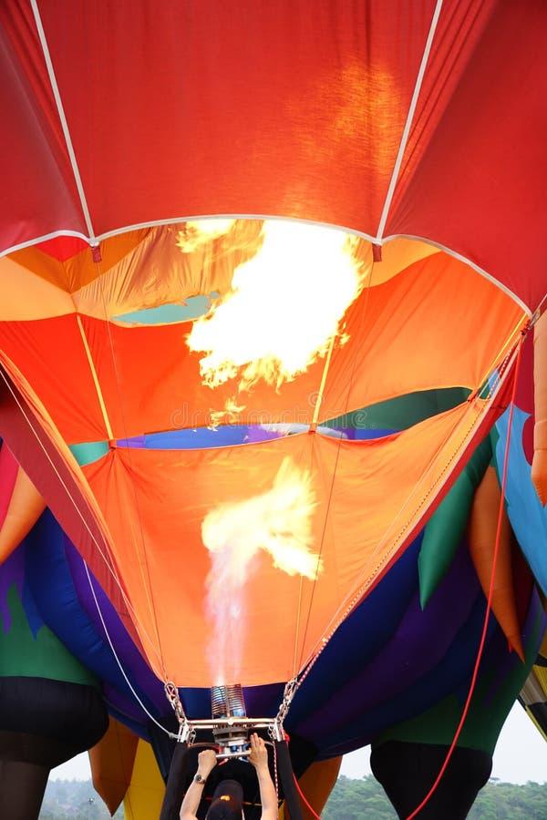 Equipe o enchimento do balão alaranjado com o ar quente imagem de stock