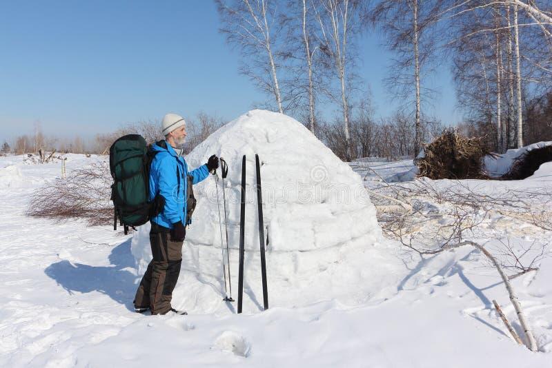 Equipe o esquiador que está por um iglu em uma clareira fotos de stock royalty free