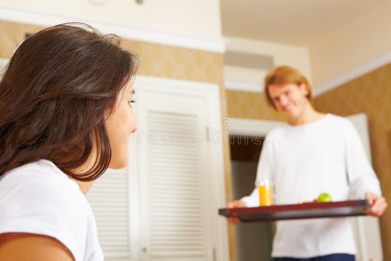 Equipe o fornecimento do pequeno almoço a seu esposo na cama fotografia de stock