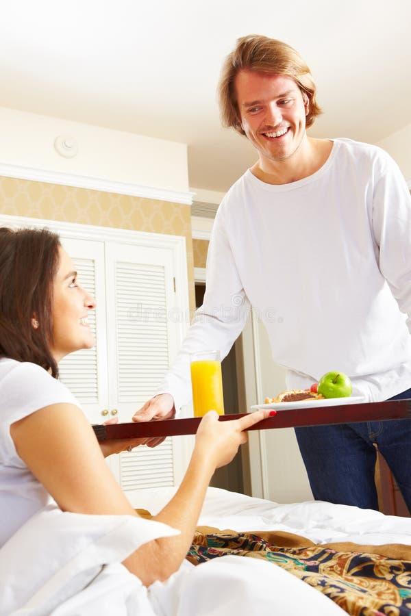 Equipe o fornecimento do pequeno almoço a seu esposo na cama foto de stock