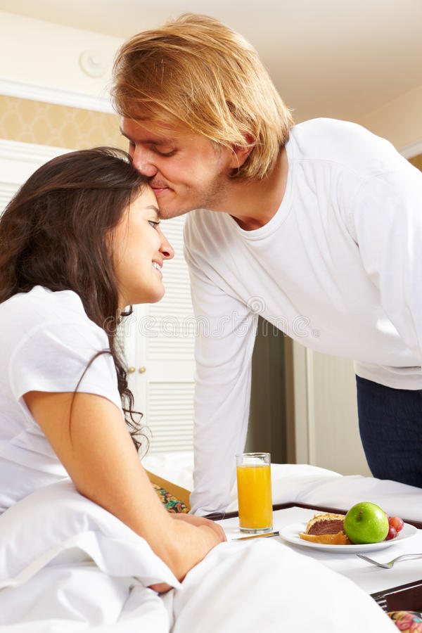 Equipe o fornecimento do pequeno almoço a seu esposo na cama imagem de stock royalty free