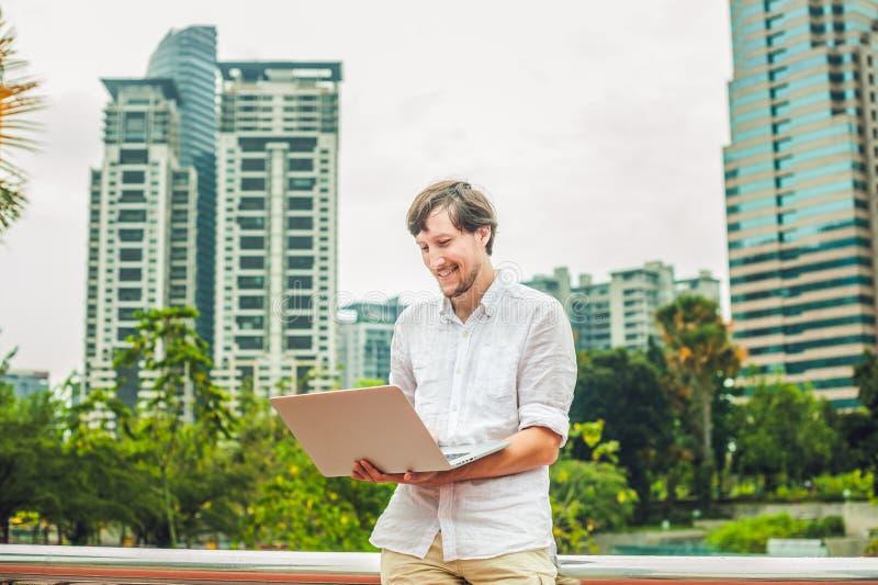 Equipe o homem de negócios ou o estudante no vestido ocasional usando o portátil em um parque tropical no fundo dos arranha-céus  foto de stock royalty free