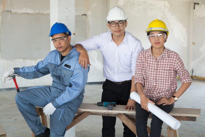 A equipe, o homem e a fêmea da indústria da construção, juntam-se ao tornado como fotos de stock