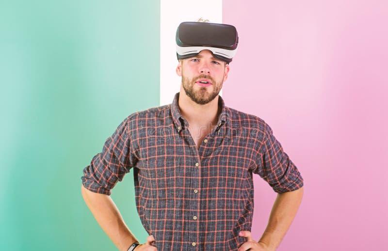 Equipe o indivíduo não barbeado com vidros de VR, fundo cor-de-rosa Tecnologias modernas do uso do moderno para o entretenimento  fotografia de stock