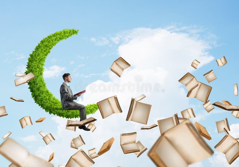 Equipe o livro de leitura e os muitos deles voo no ar foto de stock