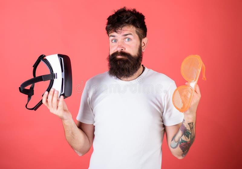 Equipe o moderno farpado com os auriculares da realidade virtual e os óculos de sol louvered no fundo vermelho Escolha entre a re foto de stock royalty free