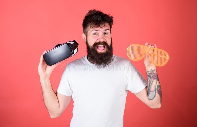 Equipe o moderno farpado com os auriculares da realidade virtual e os óculos de sol louvered no fundo vermelho Homem que faz a de foto de stock