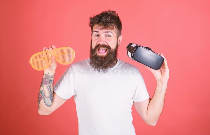 Equipe o moderno farpado com os auriculares da realidade virtual e os óculos de sol louvered no fundo vermelho Homem que faz a de imagem de stock