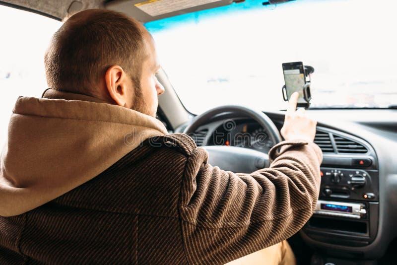 Equipe o motorista no carro que toca à mão na tela do smartphone com sistema de navegação da aplicação imagens de stock