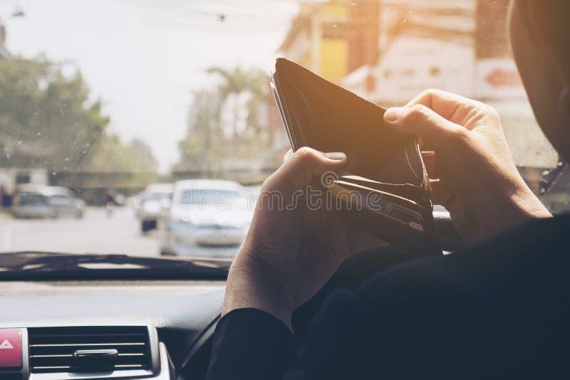 Equipe o olhar em sua carteira vazia ao conduzir o carro imagens de stock