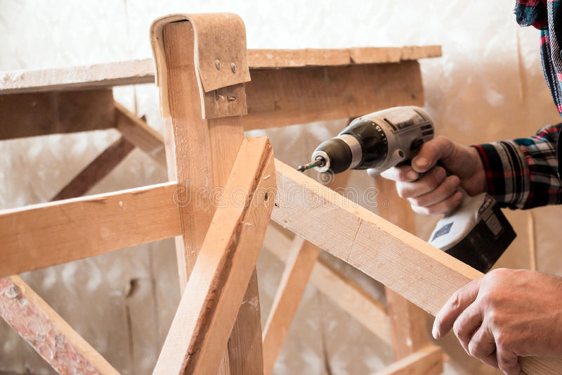 Equipe o parafusamento de um parafuso na madeira imagens de stock