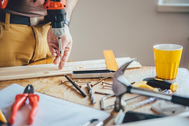 Equipe o parafusamento de um parafuso na madeira imagem de stock royalty free