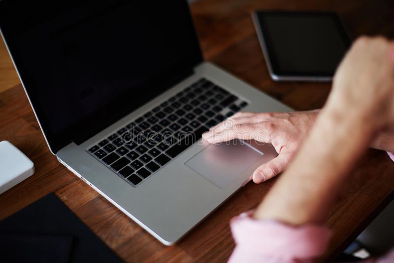 Equipe o portátil do uso que senta-se na mesa de madeira com mão contra sua boca imagens de stock royalty free