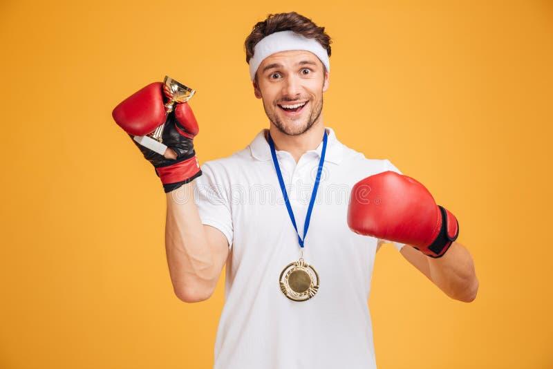 Equipe o pugilista em luvas vermelhas e a medalha que guarda o copo do troféu imagens de stock royalty free