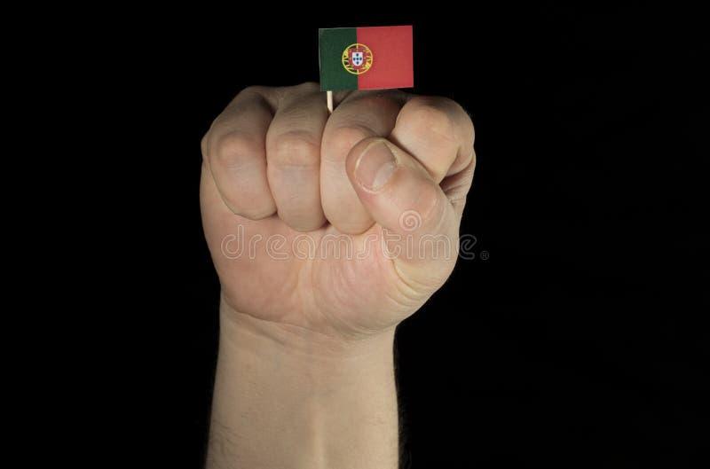 Equipe o punho da mão com a bandeira portuguesa isolada no preto foto de stock