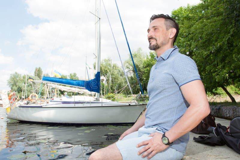 Equipe o relaxamento e a apreciação da vista na natureza e no lago Homem considerável que respira fora no fundo do barco fotos de stock royalty free