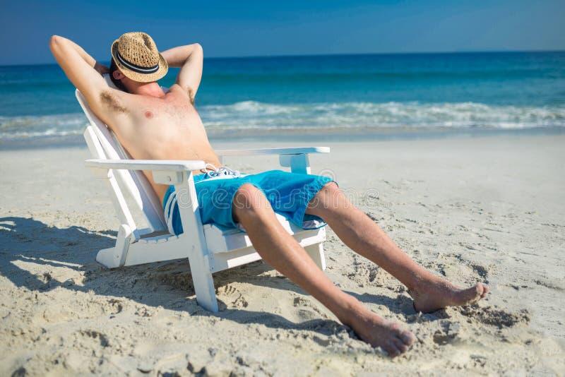 Equipe o relaxamento na cadeira de plataforma na praia imagens de stock