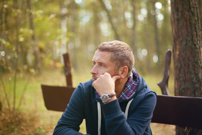 Equipe o retrato temperamental de pensamento, sentando-se no parque do outono fotografia de stock