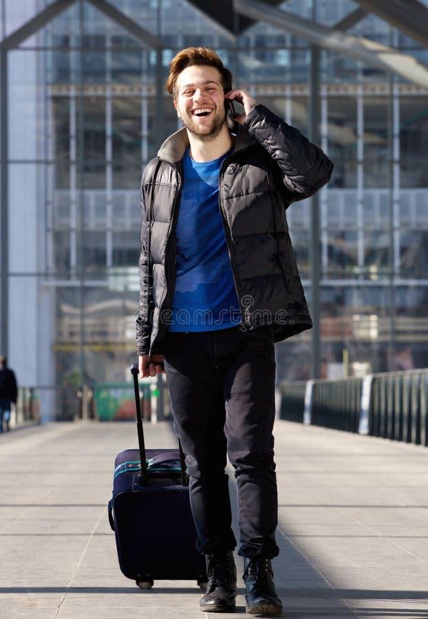 Equipe o riso no telefone celular ao andar com bagagem foto de stock royalty free