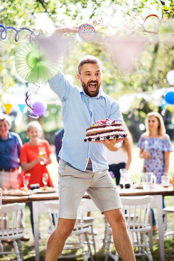 Equipe o salto com um bolo em uma celebração de família ou em um partido de jardim fora foto de stock