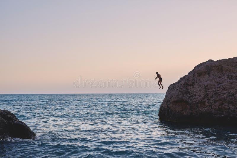 Equipe o salto no mar do penhasco foto de stock