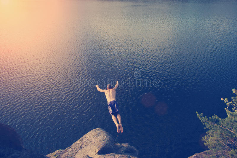 Equipe o salto no rio do penhasco imagem de stock royalty free