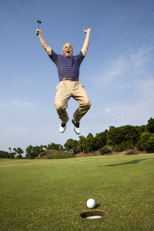 Equipe o salto para a alegria sobre o bom tiro de golfe. imagens de stock