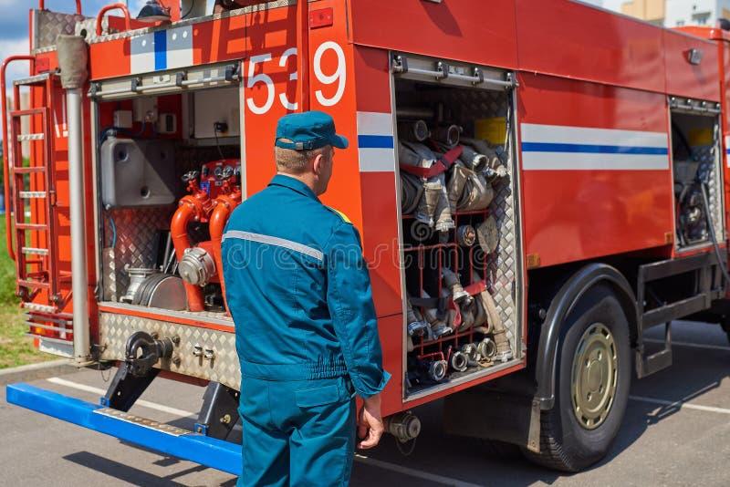 Equipe o sapador-bombeiro no fundo de um carro de bombeiros imagens de stock royalty free