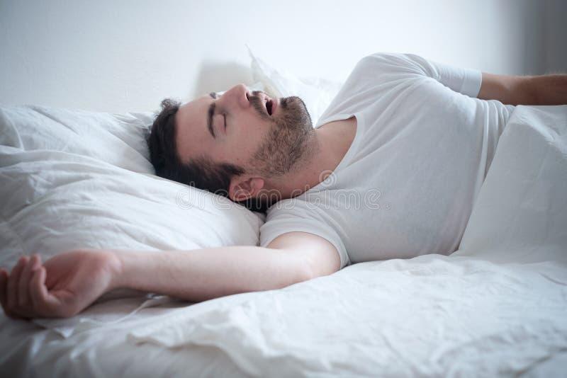 Equipe o sono em sua cama e ressonar alto fotografia de stock royalty free