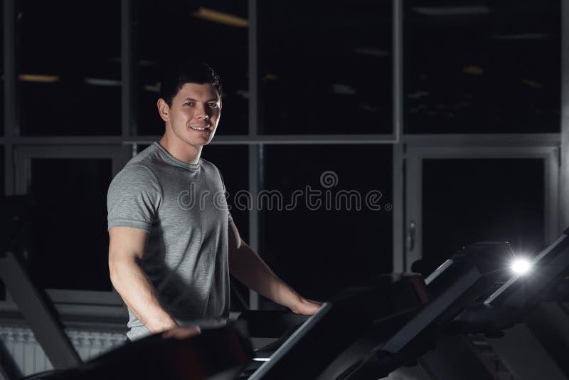 Equipe o sorriso no gym que faz o exercício na escada rolante fotos de stock royalty free