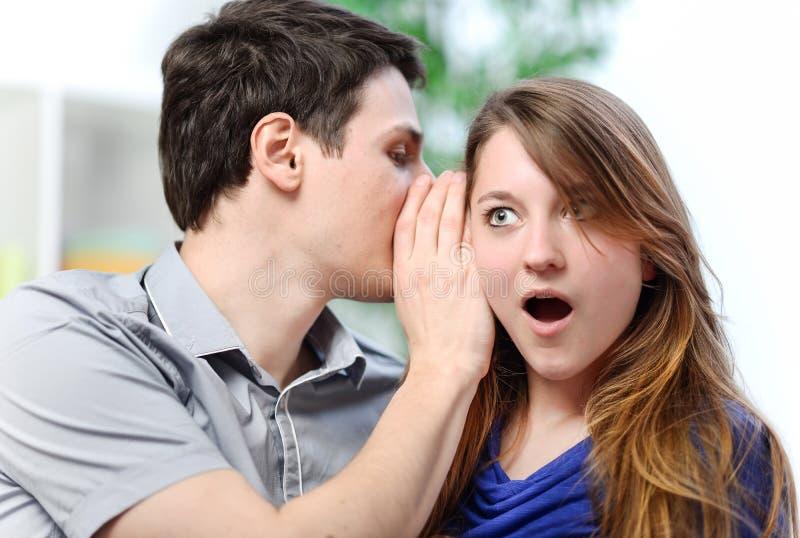 Equipe o sussurro na orelha de sua esposa surpreendida fotografia de stock royalty free