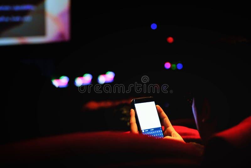 Equipe o telefone celular do uso e a imagem borrada fora da luz no teatro, fotografia de stock