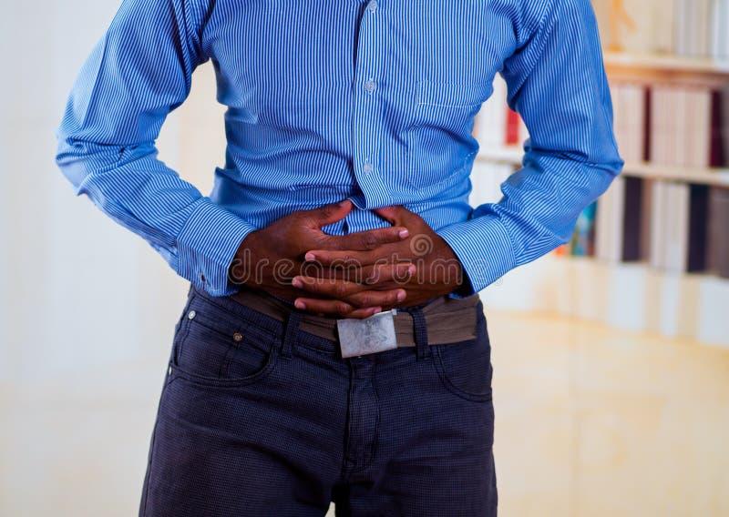 Equipe o toque com mãos de seu estômago, normalmente pessoa fazem isto quando têm a dor imagem de stock