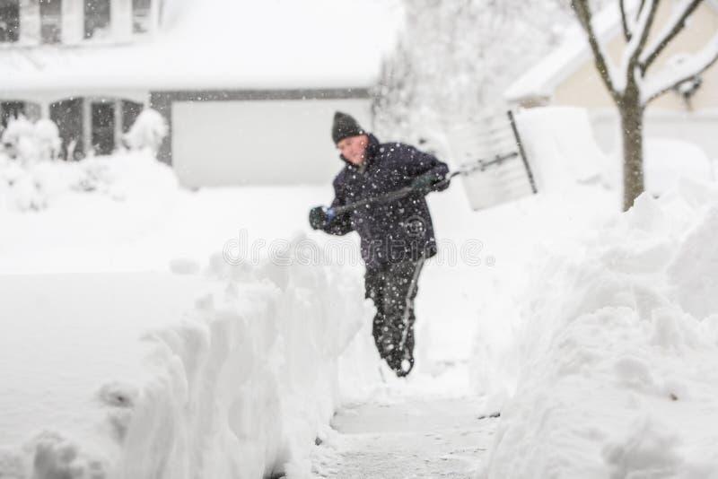 Equipe o trabalho com pá da profundidade da neve de campo rasa, foco na neve dentro para fotografia de stock royalty free