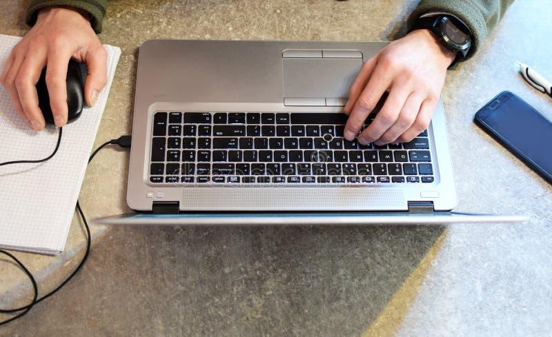 Equipe o trabalho de mãos com o portátil na tabela cinzenta foto de stock royalty free
