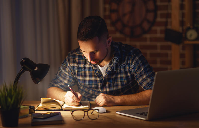 Equipe o trabalho no computador em casa na noite na obscuridade imagens de stock royalty free