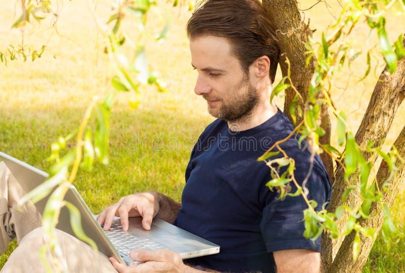 Equipe o trabalho no computador portátil exterior em um parque fotos de stock