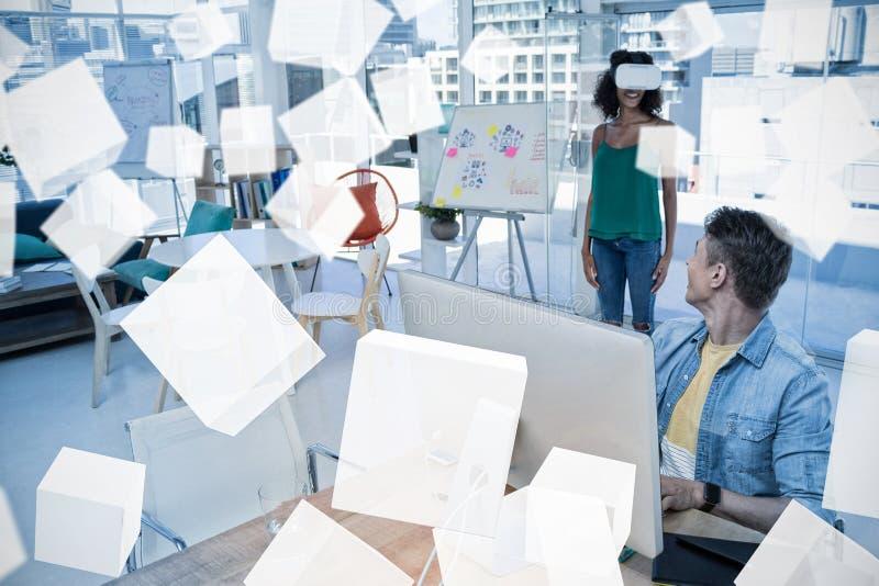 Equipe o trabalho no computador quando executivo fêmea que usa auriculares da realidade virtual fotos de stock