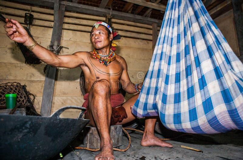 Equipe o tribo de Mentawai que senta-se perto do berço com um bebê na casa imagem de stock