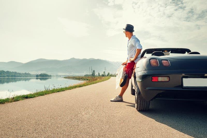 Equipe o viajante de solo no resto do carro do cabriolet na montanha pitoresca imagens de stock