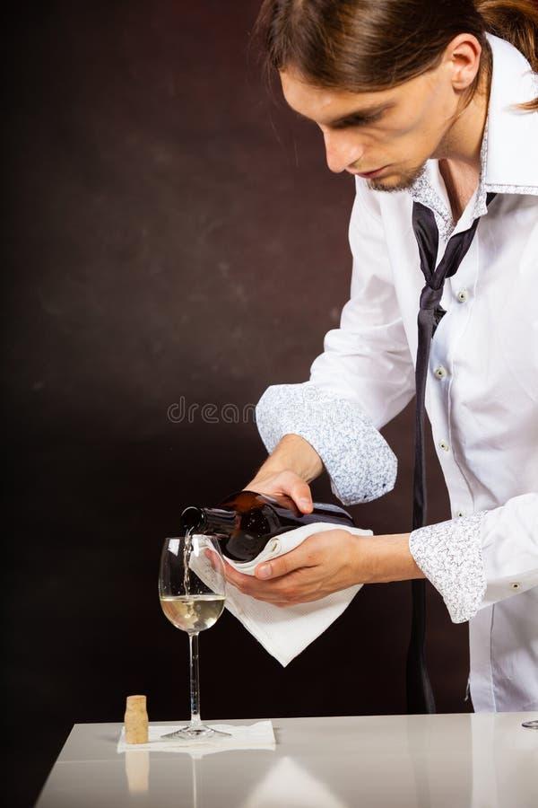 Equipe o vinho branco de derramamento do garçom no vidro fotos de stock