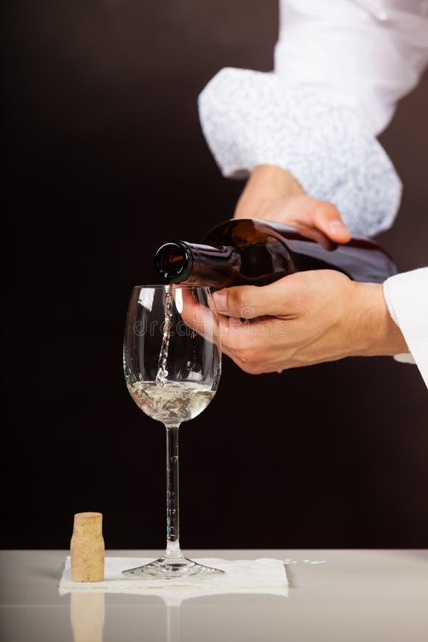 Equipe o vinho branco de derramamento do garçom no vidro fotografia de stock
