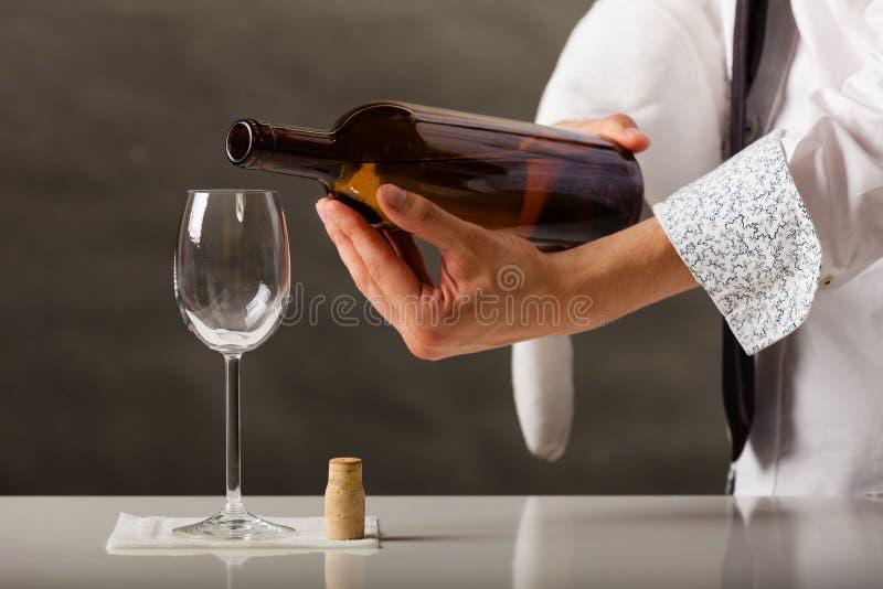 Equipe o vinho de derramamento do garçom no vidro fotos de stock